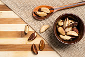Brazil nuts inside brown ceramic and wooden spoon on bamboo wooden background