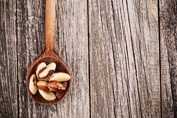 Brazil nuts on a spoon on wooden background. stock photo