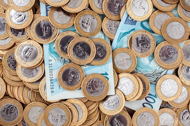 Brazilian 1 Real coins and 100 Reais bank notes Brazilian 1 Real coins and 100 Reais bank notes depreciation stock pictures, royalty-free photos & images