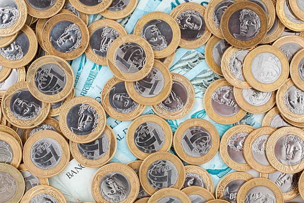 Brazilian 1 Real coins and 100 Reais bank notes stock photo