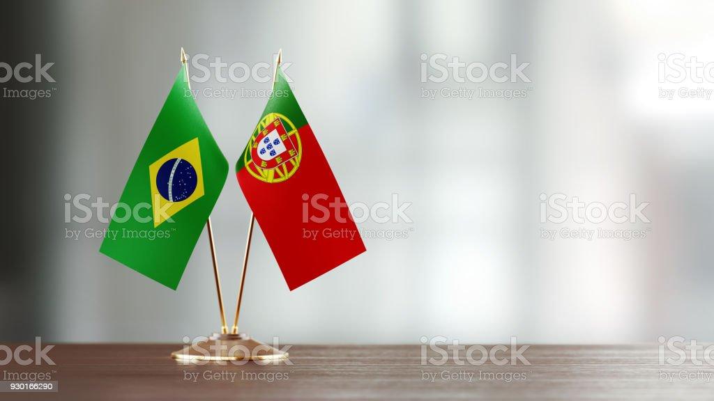 Par de la bandera brasileña y portuguesa en un escritorio sobre fondo Defocused - foto de stock