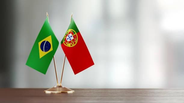 Par de bandeira brasileira e portuguesa em uma mesa sobre fundo desfocado - foto de acervo