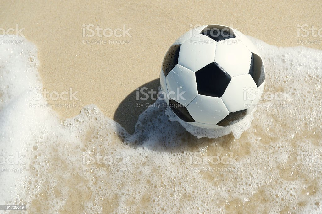 Brazilian Beach Soccer Football in the Wave stock photo