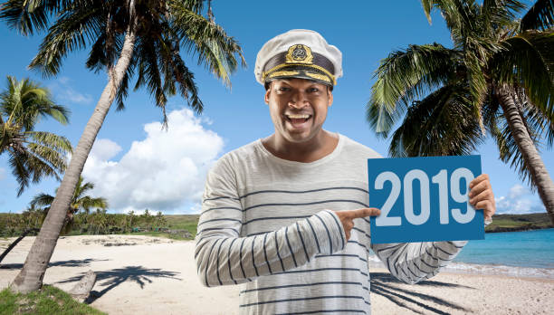 Brazilian boat captain showing billboard with new year 2019 on island Afro american captain showing billboard with new year 2019 in caribbean sea sailor hat stock pictures, royalty-free photos & images
