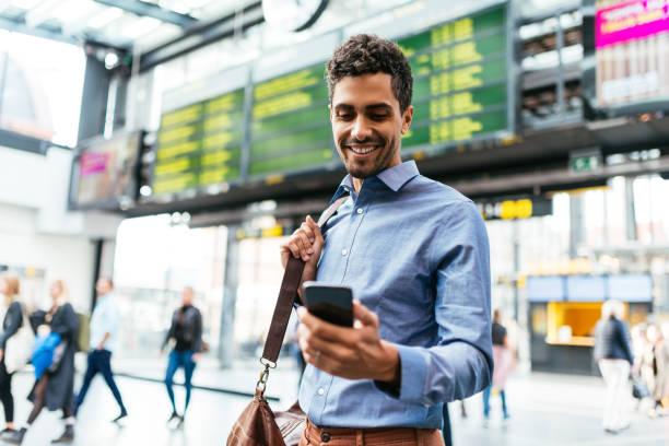 empresário brasileiro no aeroporto verificando o voo - aeroporto - fotografias e filmes do acervo