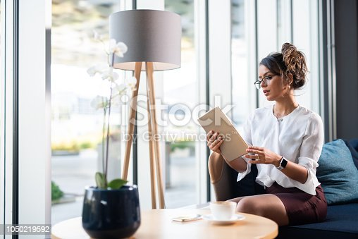 912944158istockphoto Brazilian businesswoman reading reports on iPad. 1050219592