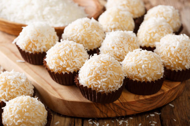 brazilian coconut kisses (beijinhos de coco  are traditionally made from a mixture of sweetened condensed milk, coconut flakes, and butter - kiss стоковые фото и изображения