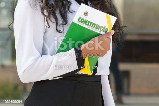 Florianópolis, Santa Catarina, Brazil - April 21, 2018: A close-up view of a woman holding the Constitution of the Federative Republic of Brazil book in Santa Catarina state, Brazil