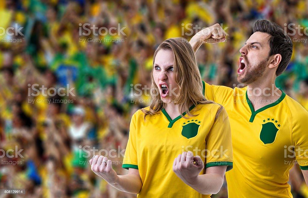 Fãs brasileiros casal celebrando no estádio - foto de acervo