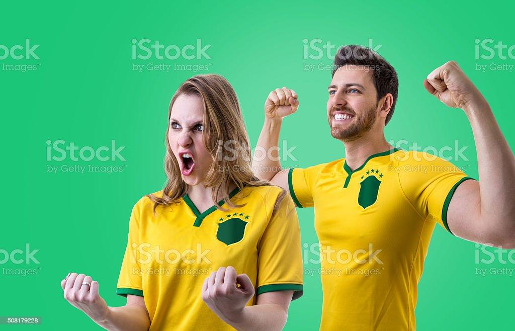 Fãs brasileiros casal celebrando sobre fundo verde - foto de acervo
