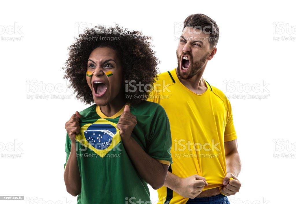 Brazilian couple fan celebrating on white background royalty-free stock photo