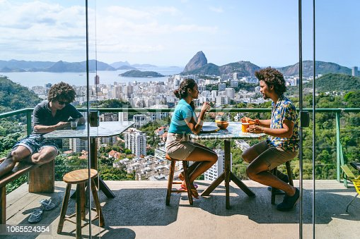 Man and woman on balcony, scenic view and city backdrop, on vacation