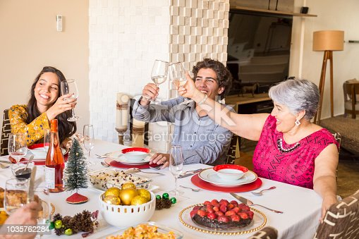 1035768506 istock photo Brazilian family sitting at dinner table celebrating Christmas together 1035762284