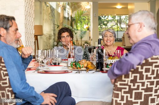 1035768506 istock photo Brazilian family sitting at dinner table celebrating Christmas together 1035765204