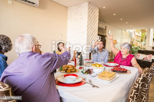 1035768506 istock photo Brazilian family sitting at dinner table celebrating Christmas together 1035765562