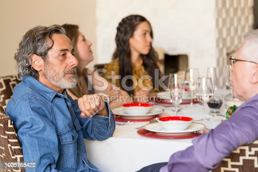 1035768506 istock photo Brazilian family sitting at dinner table celebrating Christmas together 1035768422
