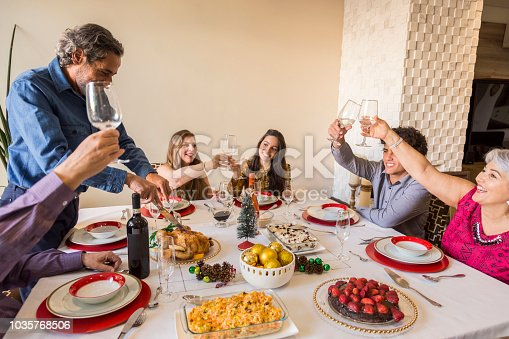 istock Brazilian family sitting at dinner table celebrating Christmas together 1035768506