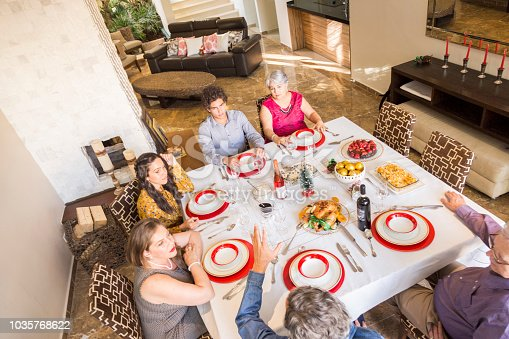 1035768506 istock photo Brazilian family sitting at dinner table celebrating Christmas together 1035768622