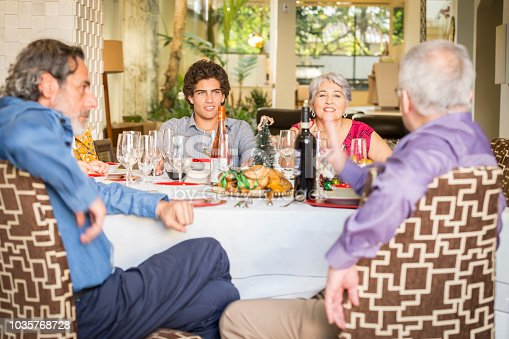 1035768506 istock photo Brazilian family sitting at dinner table celebrating Christmas together 1035768728