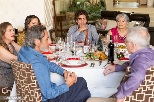 1035768506 istock photo Brazilian family sitting at dinner table celebrating Christmas together 1035768846