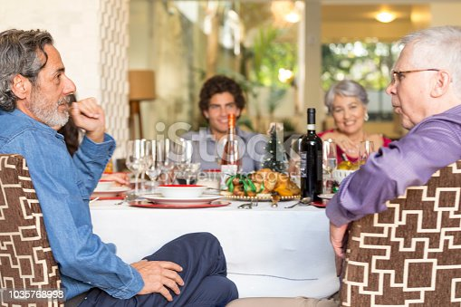 1035768506 istock photo Brazilian family sitting at dinner table celebrating Christmas together 1035768998