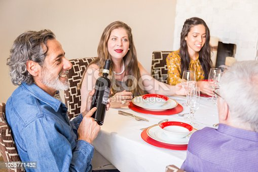 1035768506 istock photo Brazilian family sitting at dinner table celebrating Christmas together 1035771432
