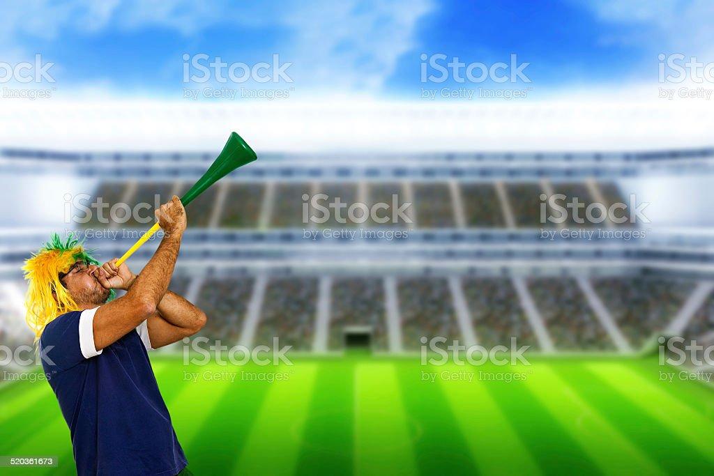 Brazilian fan at stadium playing vuvuzela stock photo
