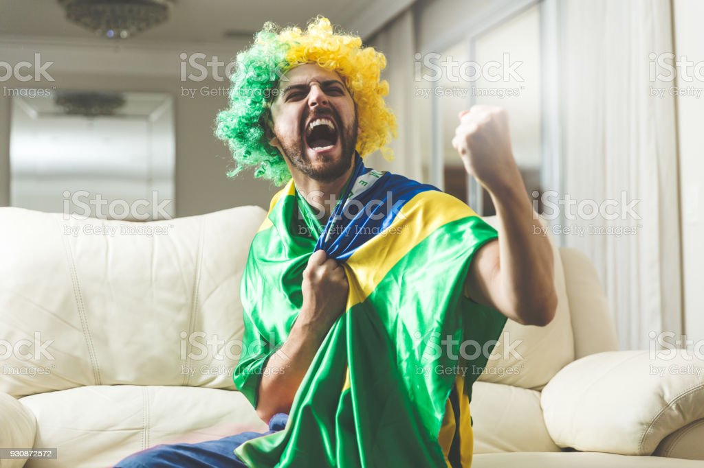 Brazilian fan celebrating at home stock photo