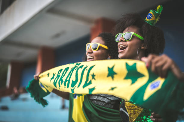 Brazilian fan friends celebrating in a soccer game stock photo