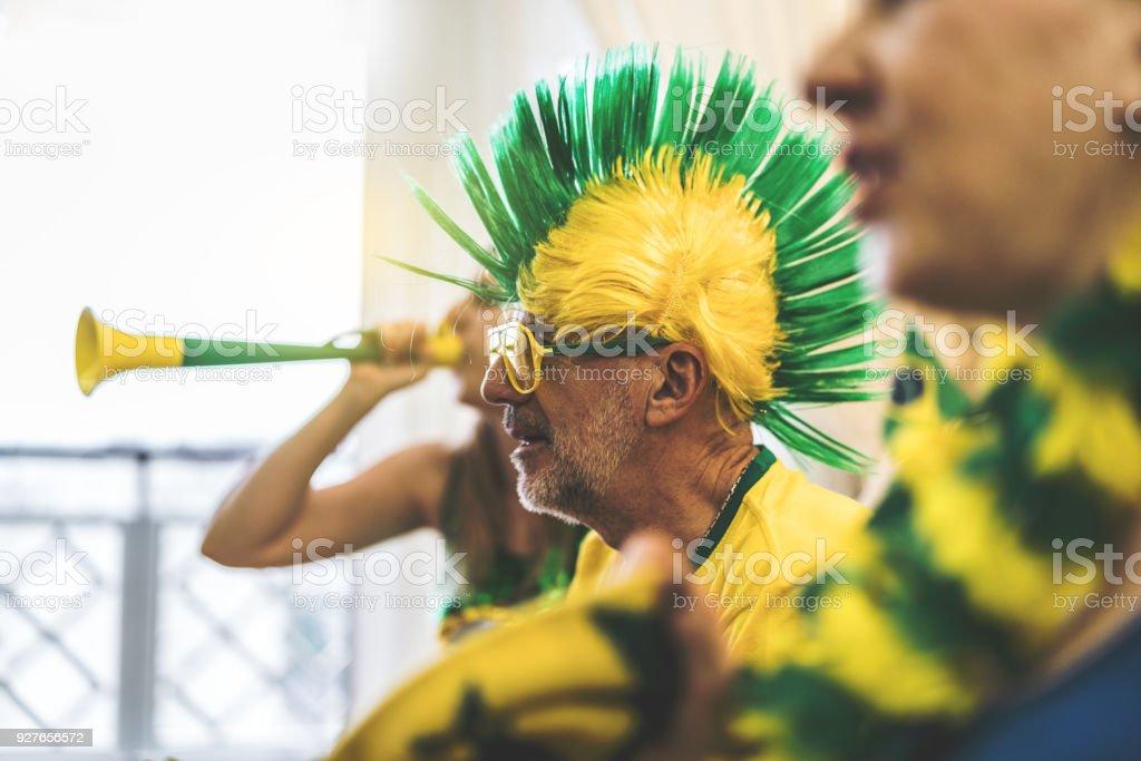 Fã brasileiro assistindo jogo de futebol em casa - foto de acervo