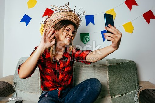 Brazilian Festa Junina at home. Person wearing typical clothes. Living room decorated with colorful flags. Woman using cellphone.