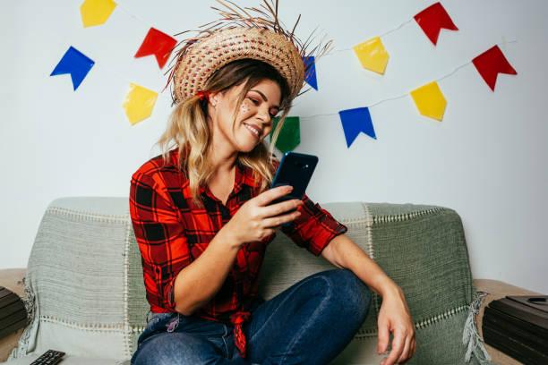 Brasilianische Festa Junina zu Hause. Person, die typische Kleidung trägt. Wohnzimmer mit bunten Fahnen dekoriert. Frau mit Handy. – Foto