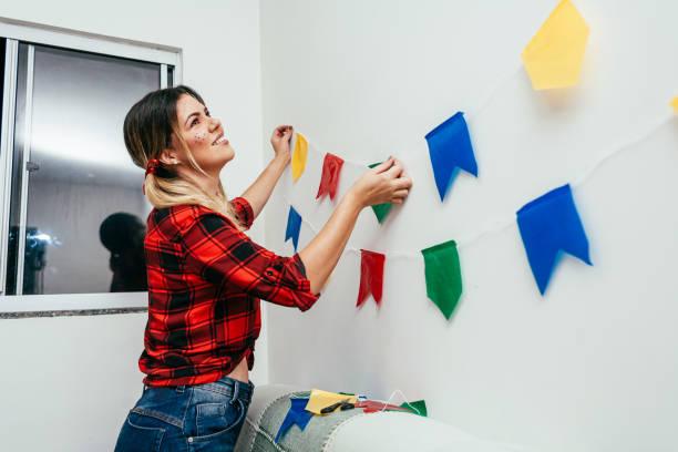 Brasilianische Festa Junina zu Hause. Person, die typische Kleidung trägt. Wohnzimmer mit bunten Fahnen dekoriert. – Foto
