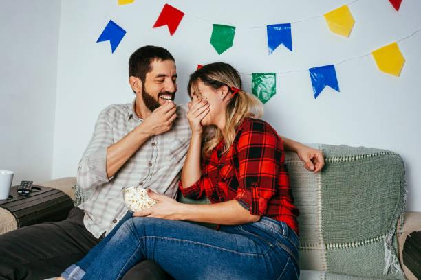 Brasilianische Festa Junina zu Hause. Person, die typische Kleidung trägt. Wohnzimmer mit bunten Fahnen dekoriert. Paar fernsehen. – Foto