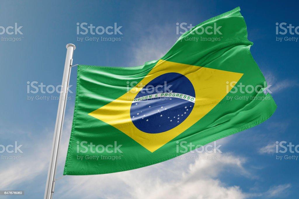 Brazilian Flag is Waving Against Blue Sky stock photo