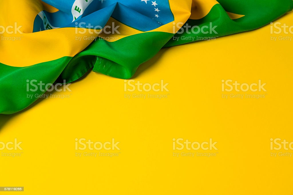 Brazilian flag on a plain yellow background - foto de acervo