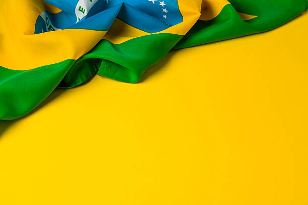 Brazilian flag on a plain yellow background stock photo