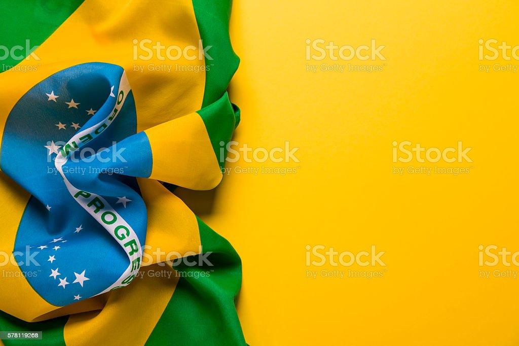 Brazilian flag on a plain yellow background stock photo