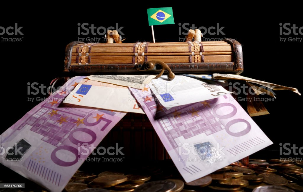 Brazilian flag on top of crate full of money stock photo