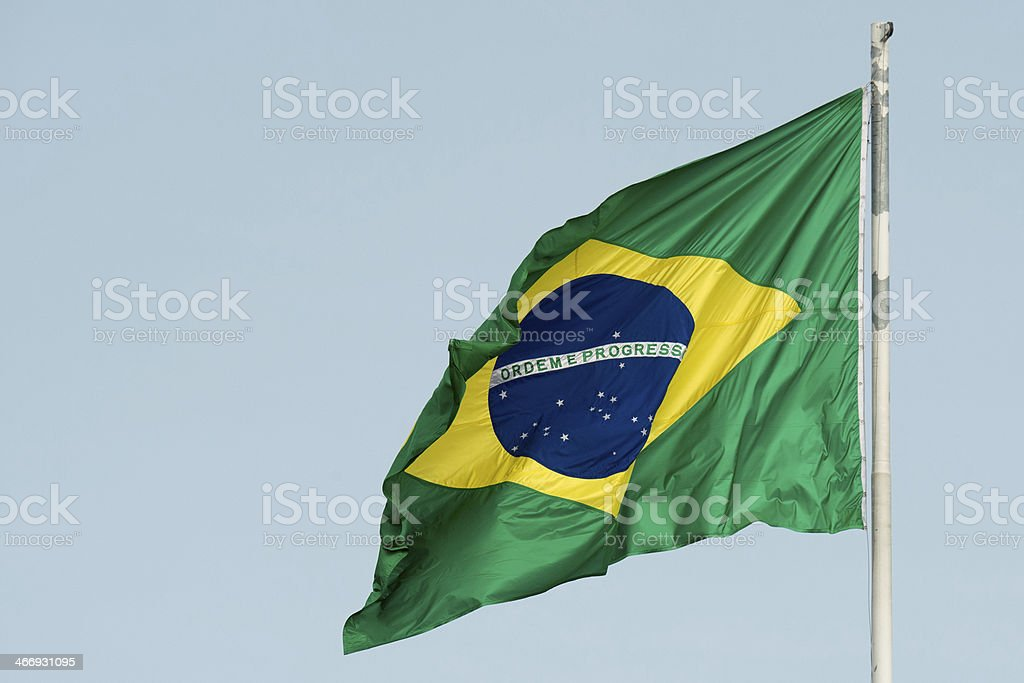 Brazilian flag unfurled against dreary gray sky stock photo