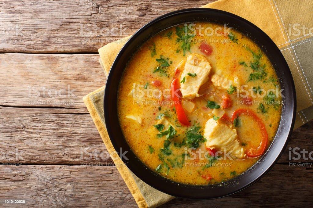 Comida brasileña: Moqueca Baiana de pescado y pimientos en primer plano de salsa picante del coco en un plato. vista superior horizontal - Foto de stock de Alimento libre de derechos