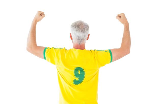 Fã do futebol brasileiro em amarelo torcendo - foto de acervo