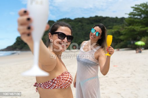 istock Brazilian Girl Friends on Celebratory Toast at Beach 1067467130