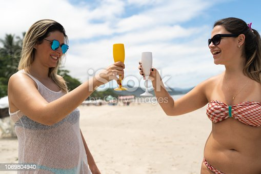istock Brazilian Girl Friends on Celebratory Toast at Beach 1069804940