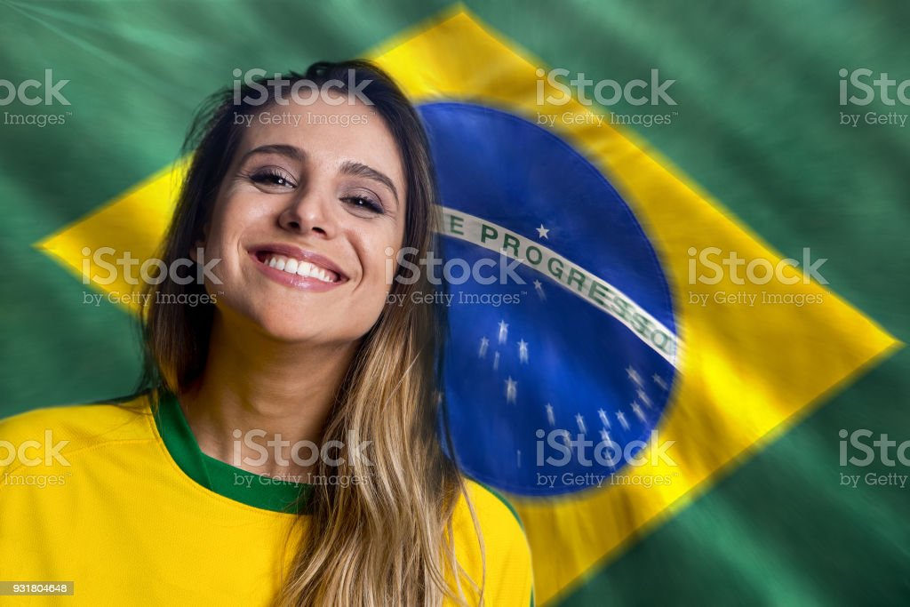 Brazilian girl smiling with a Brazilian flag on the background stock photo