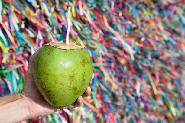 Brazilian Hand Holding Coco Gelado Wish Ribbons Salvador Bahia Brazilian hand holding coco gelado drinking coconut at wall of wish ribbons Bonfim Church in Salvador Bahia Brazil gelado stock pictures, royalty-free photos & images