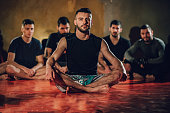 Group of men, sitting on exercise mat in gym before training.