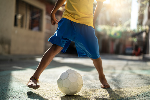 Brazilian Kid Playing Soccer in the Street