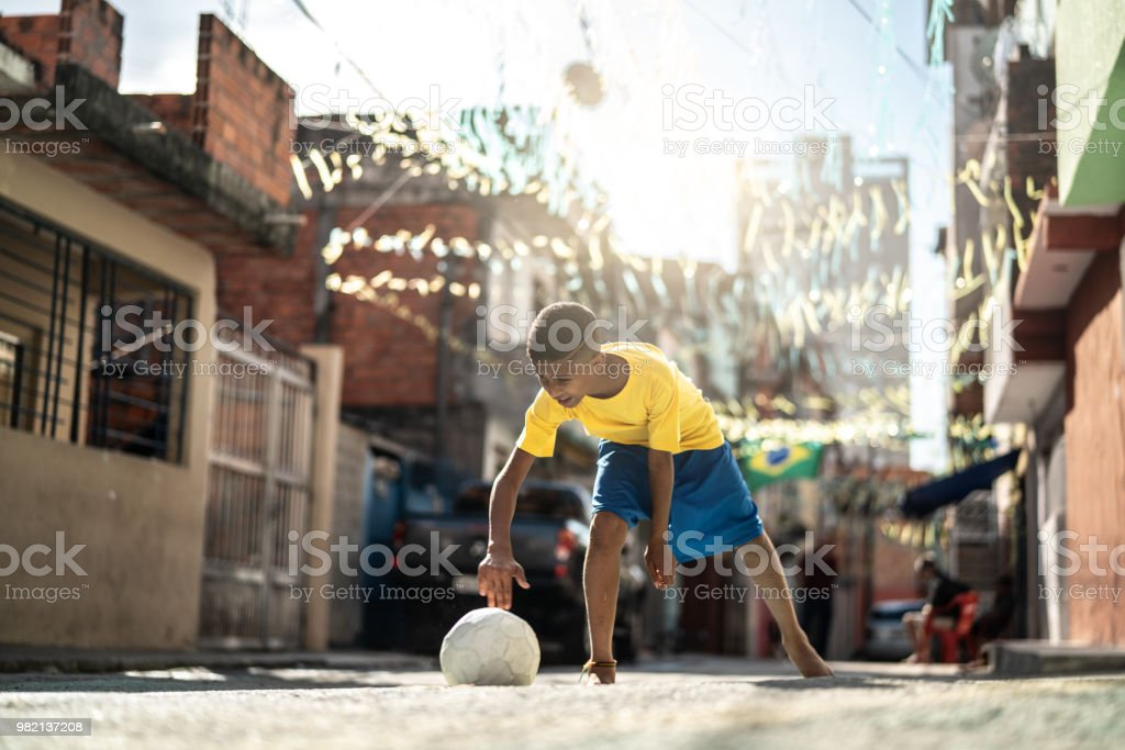 Brazilian Kid Playing Soccer in the Street stock photo
