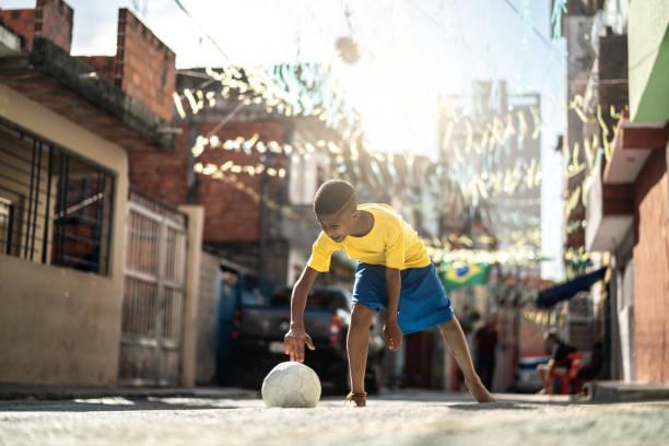 Garoto brasileiro jogando futebol na rua - foto de acervo